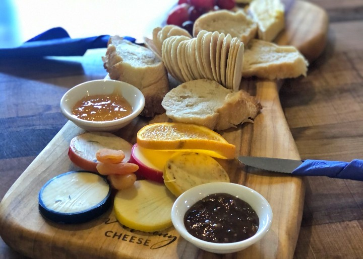 selection of cheese, crackers and chutney on wooden cheese board